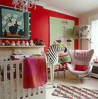 A Mark Gagnon painting of an ostrich looks down on  large toy zebra standing next to a comfortable armchair upholstered in pink tweed in this girl's bedroom
