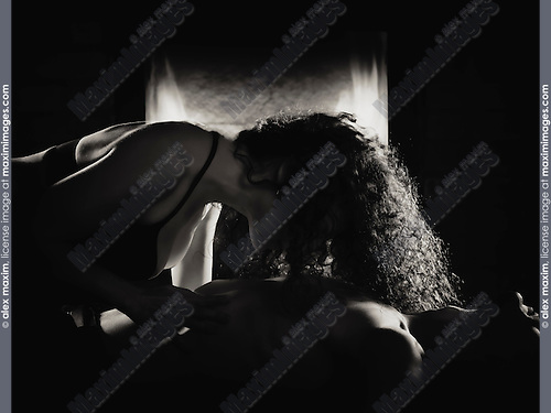 Sensual portrait of a couple making love in front of a fireplace, woman caressing man's body Black and white