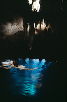 Jasai swims in the natural waters of an underground Cenote in her property, rays of light from holes in the cenote´s roof shine through the water. Photos for Jasai´s catalogue of the houses of Memo and the surrounding area