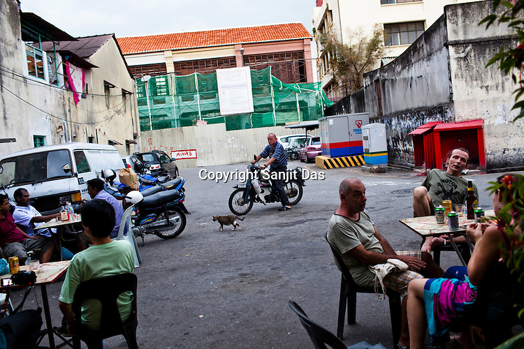 Foreign tourists and locals meet for a drink at the Antarabangsa Enterprise bar in the UNESCO heritage city of Georgetown in Penang, Malaysia. Photo: Sanjit Das/Panos