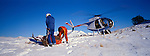 Hughs 500 C helicopter and deer hunters netting a Red Deer Stag in  snow on the Puketeraki Mountain Range Canterbury New Zealand.