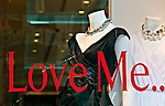 "Tommy Hilfiger Fifth Avenue store, ""Love Me .."" message written in big red letters, white black dress and white dress with chokers on mannequins, on February 28, 2010, at 681 Fifth Avenue, midtown Manhattan, NYC, New York, USA."