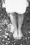 Child standing in white summer dress outdoors on grass with daisies