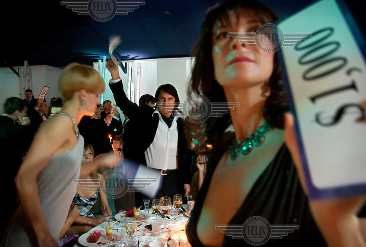 Rustam Tariko, the billionaire owner of vodka brand Russian Standard, waves mock dollar bills as he pledges a donation at a charity ball in Moscow.