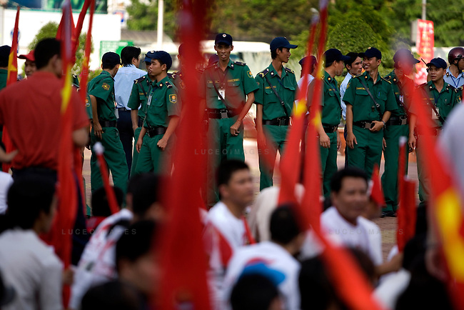 Vietnamese officers keep a watchful eye on Pro-China demonstrators as they sit in the city center waiting for the Olympic torch relay to begin in downtown Ho Chi Minh City, Vietnam. Vietnamese officials ushered anyone holding a Chinese flag into a single area and then marched the people to the starting area of the relay..Thousands of people filled the streets of downtown District 1 in Ho Chi Minh City, Vietnam, to catch a glimpse of one of the 60 torchbearers complete the last leg of the Olympic flame's global journey outside China.  The Olympic torch relay began at the Opera House in the city center and conclude at a stadium near the Tan Son Nhat International Airport, covering a route of 10-13 kilometers. The Olympic flame will head to Hong Kong next. Photo taken Tuesday, April 29, 2008. Kevin German / kevin@kevingerman.com