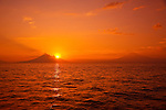 The morning sun rising behind a couple of distant volcano's... as seen from a dive site in the Fathers Reefs off New Britain Island, Papua New Guinea. A small tendril of steam rising from the 2,334 meter high summit of Mount Ulawan is a gentle reminder that we are diving in Papua New Guinea's  &quot;Ring of Fire&quot;.  Papua New Guinea has over sixty volcanoes strewn across its vast archipelago... nineteen exist on New Britain Island alone... and five of those are currently active.