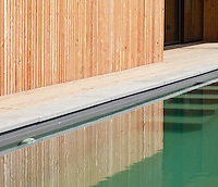 The pine cladding of the exterior wall of the property is reflected in the swimming pool