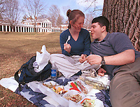 Karen Hoffman, left, and Zach Zimet, right, enjoy lunch under the shade of a tree during Fridays warm spring like day which brought a number of students to bask and play on the University of Virginia lawn in Charlottesville, VA.