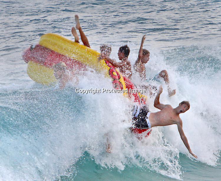 "A group of beach goers enjoy the high waves on a ""hotdog"" float at Sandy Beach in Honolulu, HI."