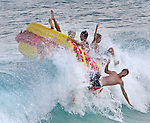 "A group of beach goers enjoy the high waves on a ""hotdog"" float at Sandy Beach in Honolulu, HI."