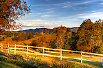 The warm light of the setting sun illuminates the fence and turning autumn leaves of the woods and farmland beyond, viewed from the front yard at Fincastle Vineyards and Winery in Fincastle, Virginia.