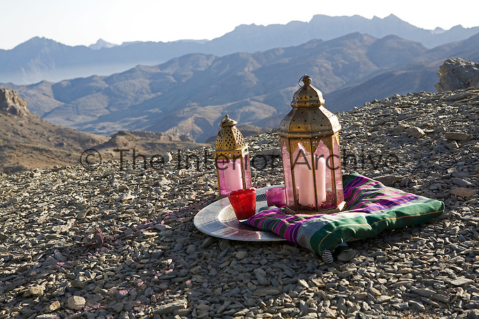 A pair of brass lanterns on a metal tray with the Jebel Ahktar mountain range in the distance