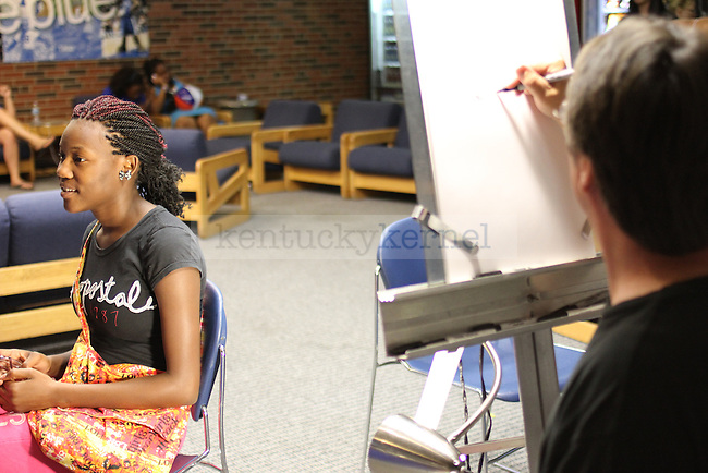 Undergraduate studies freshman Kaylin Johnson gets a caricature drawn of her at Student Center Spectacular at the Student Center on Sunday, August 19, 2012. Student Center Spectacular encouraged new students to explore the Student Center and get involved at UK. Photo by Tessa Lighty   Staff