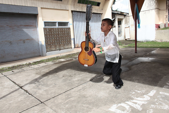 A boy guitarist runs to take his place for a performance during Philippines Independence Day celebrations in the town of Sindangan, Mindanao island, Philippines. June 12, 2011.