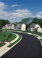 Suburban homes asphalt blacktop road surface. high angle view freshly fresh coat of asphalt paving covers street suburb suburban residential house housing real estate