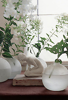 "On a window sill in the living room a tiny clay figurine entitled ""Kneeling Woman"" by Isabelle Stienon sits surrounded by frosted glass vases filled with Phlox"