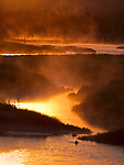 Steam rises from the Madison River as the sun rises in the sky.
