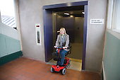 Woman driving electric mobility scooter exiting a lift at a railway station. MR