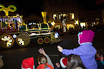 Youth wave as a train float rolls by during the Festival of Lights Parade.