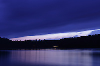 Hortonia, VT, USA - August 21, 2011: View across a lake in the evening as clouds approach mid Vermont and distant cabin lights come on