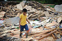 Taupik, 14, searching for plastic and metal waste for recycling amongst newly dumped waste at the 'Trash mountain', Makassar, Sulawesi, Indonesia.