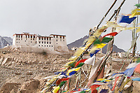 Bridge covered in prayer flags with Stakna Monastery in the background. Leh, Jammu and Kashmir, India.