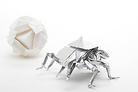 New York, NY, USA - October 27, 2011: Keith Nunas, Edmonton, Canada, designed and folded this complex Origami beetle out of one square of silver foil. In the background is a white Ishibashi ball designed by Minako Ishibashi and folded by Esme Cribb.
