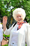 Senior woman in red white and blue waves whiles watching the Merrick Memorial Day Parade on Monday, May 28, 2012, on Long Island, New York, USA. America's war heroes are honored on this National Holiday.