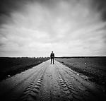 Lone male figure standing on track in flat landscape