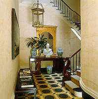 The floorboards in the imposing entrance hall have been painted in a black and gold geometric design and the walls in a trompe l'oeil stone effect