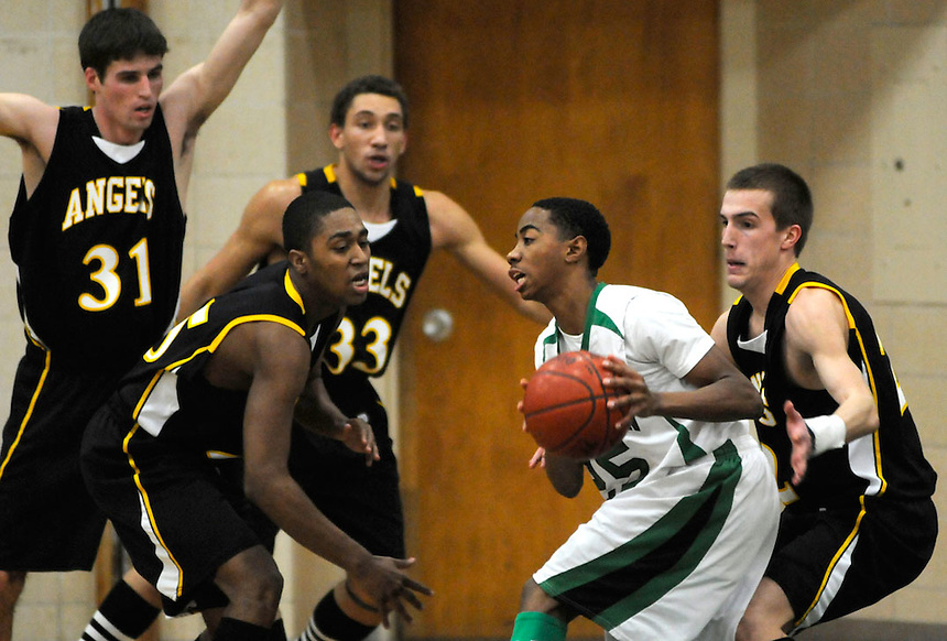 Dominican High School's Jerrel Harris is surrounded by a solid St. Catherine's defense during the game Friday night at Dominican High School on Jan. 30, 2009. For St. Catherine's are (from left) Nick Bixler (31) Steve McWhorter, Javar Lawson (33) and Jake Thomas (far right). Ernie Mastroianni photo.