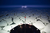 Coast Guard icebreaker Healy pushing through broken plates of ice at night, Bering Sea.