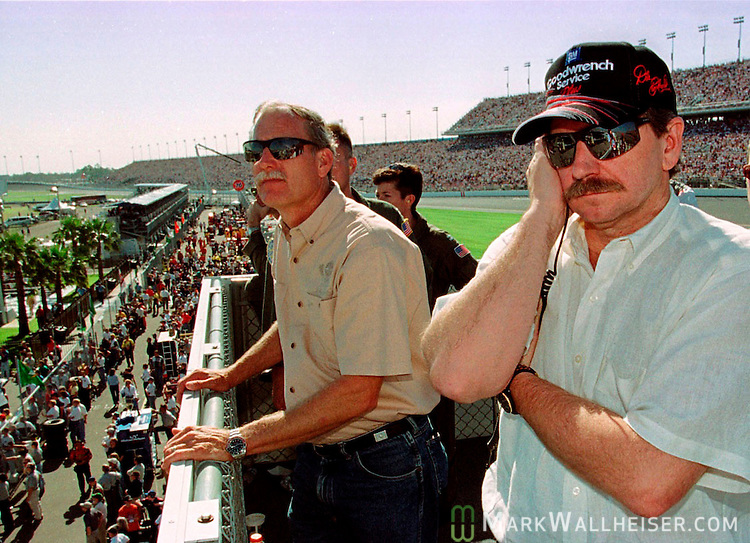 Dale Earnhardt Sr listens to his crew's radio and watches his son, Dale Earnhardt Jr., run in the Twin 125  NASCAR auto race in Junior's first year of NASCAR racing.  Dale Earnhardt Sr won his first and only Daytona 500 later that week..