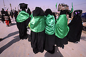 KARBALA, IRAQ: Shia pilgrims cover themselves in green...Shia pilgrims pray during the last day of the Ashura festival...Photo by Metrography