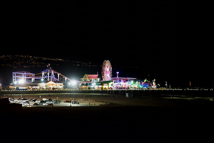 Parking of vehicles on the beach and the amusement park of the Santa Monica Pier at night in Los Angeles