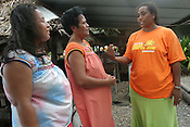 In the village of Tenoraereke Greenpeace Climate Change campaigner Koin Etuati (on right of picture) talks to school teacher Beiataake Orea (centre) and another villager, about climate change and global warming, on the Pacific island of Kiribati.