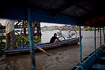 "A man crosses the Hau Giang River, a tributary of the Mekong River, with his bicycle in Chau Doc, in the An Giang Province, Vietnam. When the Mekong River reaches Vietnam it splits into two smaller riveres. The ""Tien Giang"", which means ""upper river"" and the ""Hau Giang"", which means ""lower river"". Photo taken on Monday, December 7, 2009. Kevin German / Luceo Images"
