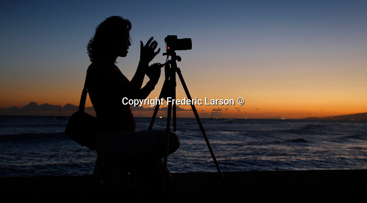 A photographer is silhouette by the evening twilight on Magic Island on the island of Oahu in Honolulu, Hawaii.