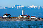 The Dungeness Spit lighthouse as seen from the water in the Strait of Juan de Fuca. Behind are the Olympic Mountains in Olympic National Park, which sometimes get between 30 and 60 feet of snow in the winter. The lighthouse sits near the end of Dungeness Spit, a 5 mile long sandbar reaching out into the Strait.