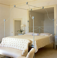 The painted wrought-iron bedstead in the master bedroom was designed by Luisa Beccaria and made in northern Italy