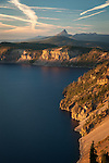 Sunset over Crater Lake from the east rim with volcanic peaks in the background