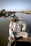 Marsh Arabs. Southern Iraq. Circa 1985. Marsh Arab man in boat with  adobe homes  banks of river Tigris.