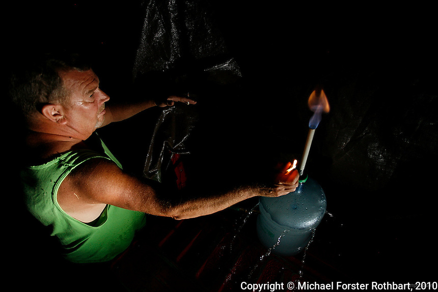 Can you light your water on fire? Bill Ely of Dimock, Pennsylvania can.<br /> <br /> The  Elys are among 14 families near Carter Road in Dimock whose drinking water wells became contaminated with methane and other chemicals after gas drilling on their properties. Cabot Oil and Gas, the company held responsible by the Pennsylvania Department of Environmental Protection, has had at least 21 spills in Dimock township in less than two years. The Elys' well has so much methane that the water appears carbonated and Bill regularly lights his water on fire to show visitors.<br /> <br /> Hydraulic fracturing or &quot;fracking&quot; is new method of drilling for natural gas: millions of gallons of water, sand and proprietary chemicals are pumped down a well under high pressure. The pressure fractures the shale, opening fissures so that natural gas can flow more freely. In August 2010, fracking is being widely used in the Marcellus Shale formation under Pennsylvania while New York considers a moratorium until the environmental effects can be reviewed. <br /> <br /> The 2005 Energy Policy Act exempted natural gas drilling from the Safe Drinking Water Act (plus some regulations of the Clean Water Act and Clean Air Act), and exempts companies from disclosing the chemicals used during fracking. Scientists have identified volatile organic compounds (VOCs) such as benzene, ethylbenzene, toluene, methane and xylene that have been found in contaminated drinking water near drilling sites. Other environmental concerns include surface water contamination, air pollution, forest fragmentation, plus human health problems. On the other hand, gas companies and property owners stand to earn up to one trillion dollars in profits from drilling in the Marcellus Shale.<br /> <br /> &copy; Michael Forster Rothbart<br /> www.mfrphoto.com <br /> 607-267-4893 o 607-432-5984<br /> 5 Draper St, Oneonta, NY 13820<br /> 86 Three Mile Pond Rd, Vassalboro, ME 04989<br /> info@mfrphoto.com<br /> Photo by: Michael Forster Rothbart<br /> Date: 8/2010    File#:  Canon 5D digital camera frame 70054