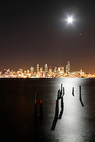 Full moon rising over Seattle city skyline at night, pilings silhouetted by moon light reflected in Elliot Bay, Seattle, Washington, USA