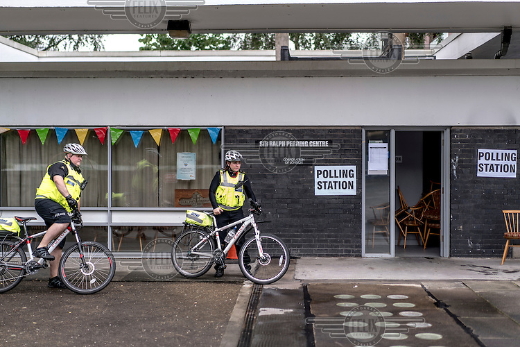 Police officers, travelling by bicycle, leave a polling station in the City of London on the morning of the EU referendum.