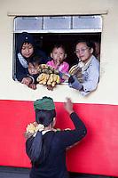 Myanmar, Burma.  Passengers in Coaches at Kalaw Train Station Bargaining with Banana Vendor.
