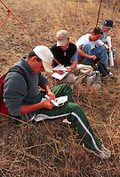 Orienteering classroom outdoors - teenaged male students plotting a course on orienteering hike. High School Students. Arizona.