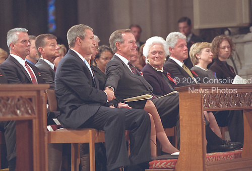 After speaking at the service for America's National Day of Prayer and Remembrance at the Washington National Cathedral in Washington, D.C. on Friday, September 14, 2001, United States President George W. Bush grasps the hand of his father, former President George H.W. Bush. Also visible in the photo are former First Lady Barbara Bush, former U.S. President Bill Clinton, U.S. Senator Hillary Rodham Clinton (Democrat of New York), and Chelsea Clinton..Mandatory Credit: Eric Draper - White House via CNP.