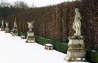 Sculptures and urns line the snow-covered path beside this beech hedge