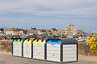 Large plastic recycling bins, dechetterie, for plastic, paper, glass spoil the view in Barfleur in Normandy, France